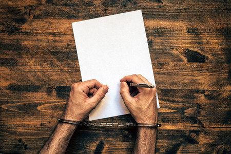 confession: Male hands cuffed signing confession, top view of police investigator detective desk Stock Photo