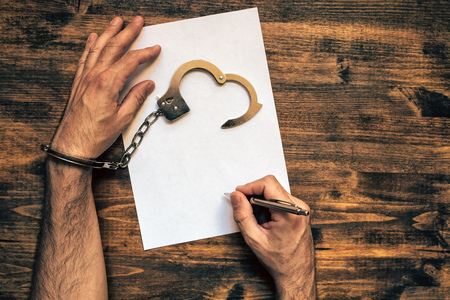 cuffed: Male hands cuffed signing confession, top view of police investigator detective desk Stock Photo