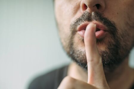 shhh: Finger on lips as man gesturing shhh sign, please be silent concept with selective focus