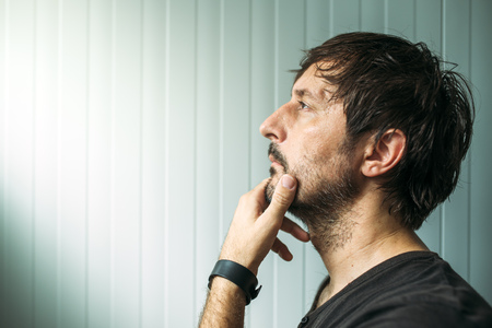 judging: Pensive unshaven man with hand on chin making decision, judging or evaluating something, studio profile portrait with copy space