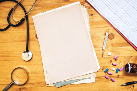 medical practitioner: Assorted office supplies on doctors desk. General medical practitioner workspace as copy space, top view. Stock Photo