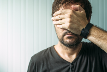 covering the face: Portrait of casual adult male covering face and eyes with hand, selective focus Stock Photo