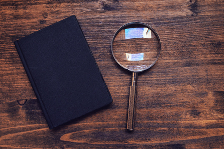 vintage objects: Loupe magnifying glass and notebook on wooden desk, top view, concept of searching and investigating Stock Photo