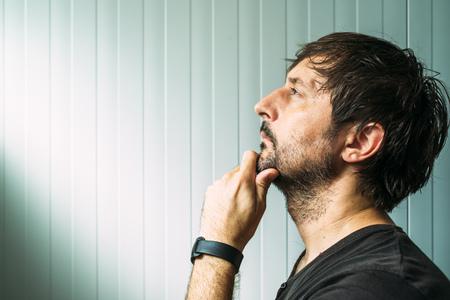 あごの意思、判断または評価コピー スペースとスタジオの横顔の肖像画、何かに手で物思いにふける無精ひげを生やした男