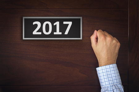 knocking: New year resolutions, businessman knocking on the office door with number 2017. Stock Photo