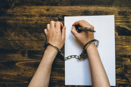 Female hands cuffed signing confession, top view of police investigator detective desk Stock Photo