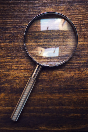 Loupe magnifying glass on wooden desk, top view, concept of searching and investigating