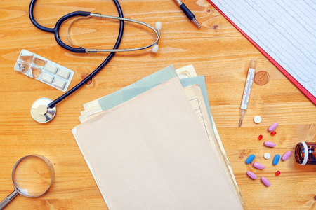 general practitioner: Assorted office supplies on general medical practitioner work desk. Doctors workspace as copy space, top view. Stock Photo