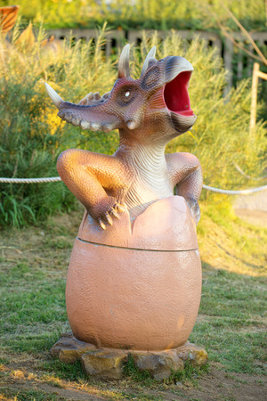 big bin: NOVI SAD, SERBIA - AUGUST 5, 2016: Small dinosaur trash bin toy from themed entertainment Dino Park in Novi Sad. Editorial