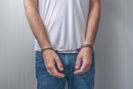 suspected: Arrested man with cuffed hands. Unrecognizable male person in jeans with handcuffs held in police station for being suspected of a crime.