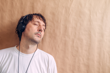 adult wall: Adult male enjoying listening to favorite music podcast on headphones, man with closed eyes leaning onto wall and relaxing.