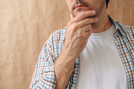 tough: Man stroking chin and thinking deep thoughts, making tough decisions