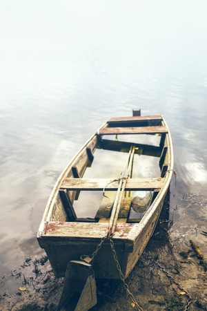 Old fishing boat on riverbank filled with water, river surface as copy space