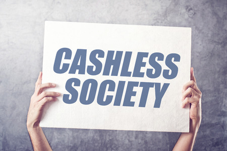 title hands: Hands holding banner with Cashless society title, concept of promoting mobile and electronic payments without cash money banknotes Stock Photo