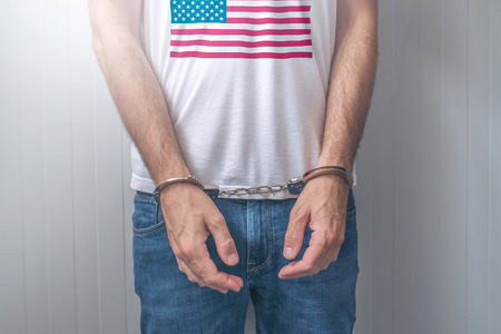 handcuffed: Arrested man with cuffed hands wearing shirt with USA flag. Unrecognizable male person in jeans with handcuffs held in police station for being suspected of a crime.