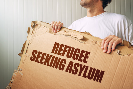 illegal immigrant: Refugee seeking asylum in foreign country, male immigrant with cardboard banner