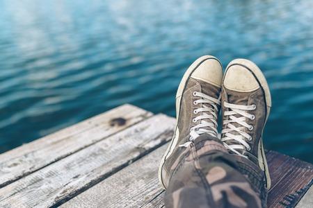 胡坐川岸桟橋、夏の午後、選択と集中で川に座ってスニーカーを着てカジュアルな若い男にリラックスを持つ男