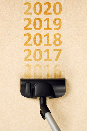 top year: Top view of vacuum cleaner sweeping number 2016 from the carpet for Happy new 2017 year concept