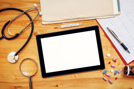 general practice: Tablet computer with blank screen on doctors office desk as copy space, top view of general medical practitioner accessories in workspace.