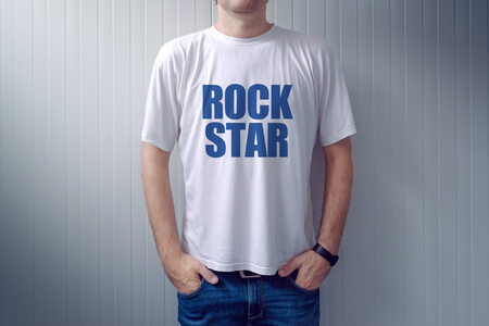 midlife: Casual adult male wearing t-shirt with Rock Star title, man in jeans leaning on the wall