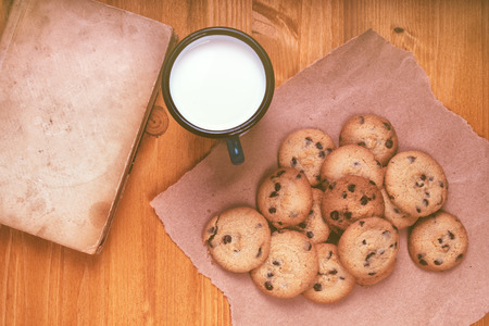 chocolate chip cookies: Homemade chocolate chip cookies, milk cup and vintage book on rustic wooden table, top view