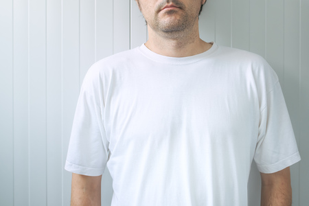 nonchalant: Casual adult male wearing blank white t-shirt as copy space for graphic design mock up