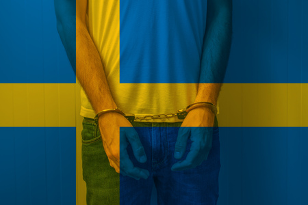 incarcerated: Arrested man with cuffed hands wearing shirt with Swedish flag. Unrecognizable male person in jeans with handcuffs held in police station for being suspected of a crime.