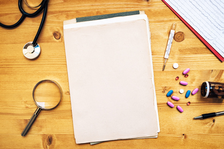 medical practitioner: General medical practitioner work desk as copy space. Doctors workspace with assorted office supplies such as stethoscope, loupe, thermometer, pencil, tablets and pills, top view. Stock Photo