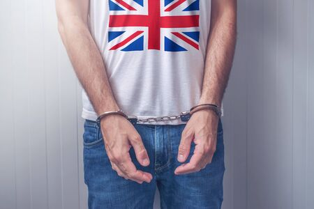 being arrested: Arrested man with cuffed hands wearing shirt with United Kingdom flag. Unrecognizable male person in jeans with handcuffs held in police station for being suspected of a crime. Stock Photo