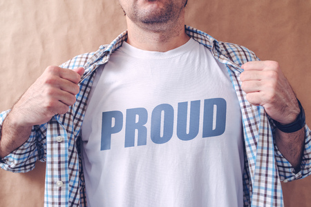 arrogance: Guy revealing his shirt with proud title, pride and arrogance concept.