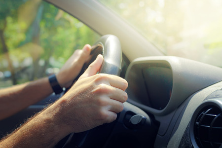 safe driving: Male hands holding car steering wheel the right way for safe driving