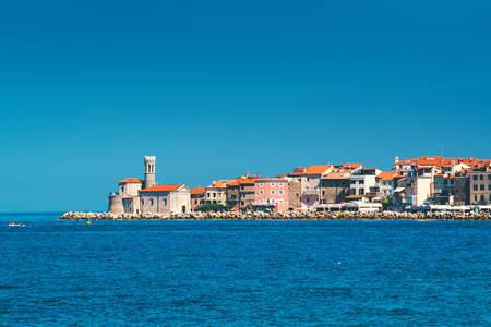 slovenian: Picturesque old town Piran on Slovenian adriatic coast, shot from sailing boat on sunny summer day Stock Photo