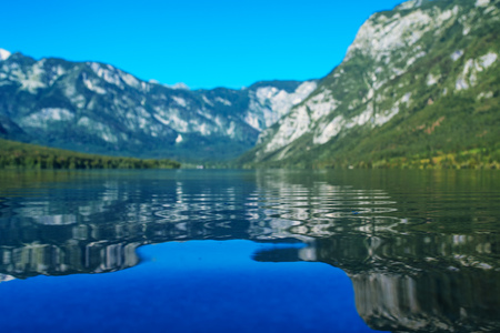 bohinj: Bohinj lake in Slovenian national park Triglav with its clear water surface surrounded with Julian Alps mountains Stock Photo