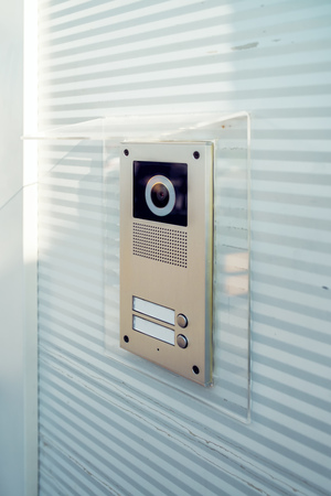 intercom: Video intercom device on building exterior wall for house entry and communication
