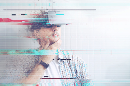 glitch: Man with VR goggles watching 360 video, digital glitch effects added in post production. Stock Photo