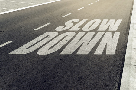 slower: Slow down speed limit sign on highway, road safety and preventing traffic accident concept.