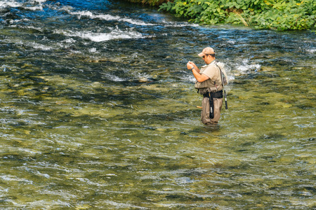 bohinj: RIBCEV LAZ, SLOVENIA - AUGUST 22, 2016: Unidentifiable man fishing at Jezernica, second shortest river in Slovenia, flowing from Lake Bohinj for 100 meters to join Mostnica and form Sava Bohinjka.