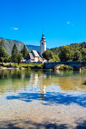 bohinj: BOHINJ LAKE, SLOVENIA - AUGUST 24, 2016: Church of St. John the Baptist at Bohinj Lake is over 700 years old and is a beautiful example of Middle Age architecture and fresco painting in Slovenia.