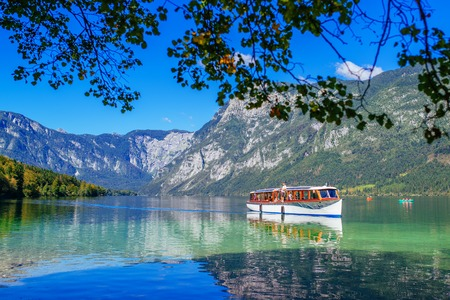 bohinj: RIBCEV LAZ, SLOVENIA - AUGUST 24, 2016: Tourists sightseeing Slovenian Bohinj lake and surrounding in Triglav national park from tourist boat