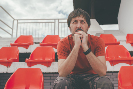 disbelief: Disappointed man at sport stadium watching the game in disbelief while his team is losing the match