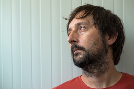 disappoint: Profile portrait od sad and disappointed man with unshaven beard looking toward the light coming from room window Stock Photo