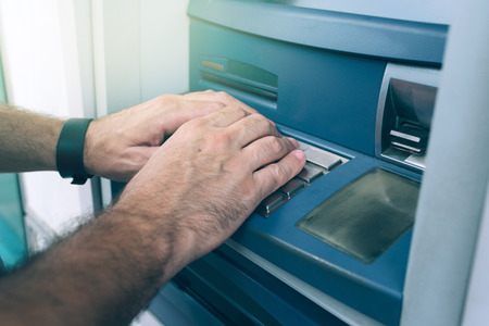 withdrawal: Hands typing PIN at ATM machine for cash money withdrawal