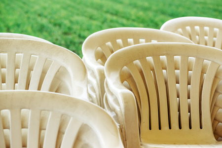 Stacked plastic chairs outdoors, selective focus detail Stock Photo