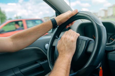 cuernos: conductor masculino nervioso que empuja el coche cuerno en la hora punta de tráfico, de cerca con el foco selectivo en la mano en el volante Foto de archivo