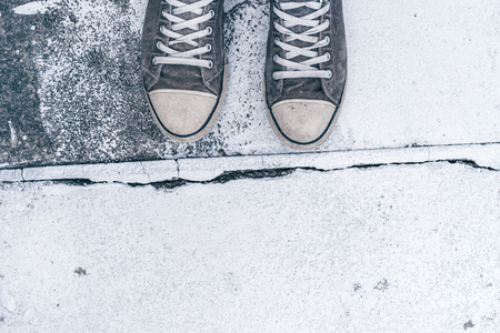 street life: Young man standing on the street, top view of worn gray sneakers on concrete floor with crack line as border - concept of obstacles, difficulties, hardship and restrictions in life. Stock Photo