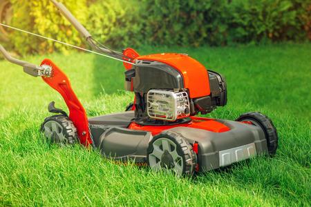 petrol powered: Modern petrol powered rotary push grass lawn mower in house backyard