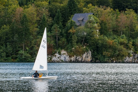 RIBCEV LAZ, SLOVENIA - AUGUST 22, 2016: Unidentifiable man sailing at Bohinj lake, located in Slovenian national park Triglav, famous location for various outdoor sport activities.