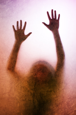 hands behind back: Trapped woman concept with back lit silhouette of hands behind matte glass, useful as illustrative image for human trafficking, prostitution, imprisonment, mental illness, captivity, depression. Stock Photo