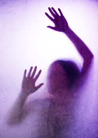 prostitution: Trapped woman concept with back lit silhouette of hands behind matte glass, useful as illustrative image for human trafficking, prostitution, imprisonment, mental illness, captivity, depression. Stock Photo