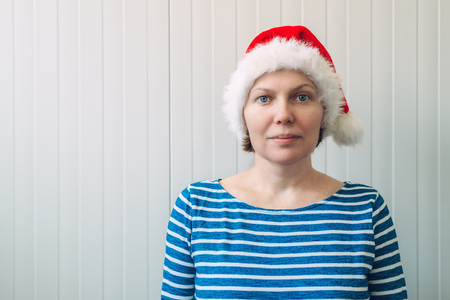 adult wall: Portrait of beautiful adult caucasian woman with Santa Claus hat against white plastic wall as copy space Stock Photo